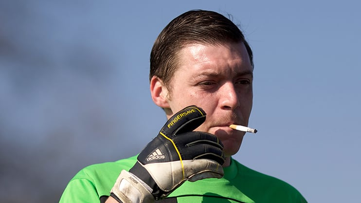 A man smokes a cigarette during a break in play during a league match between Boleyn FC (in Sky Blue) and Cranham (in Orange)